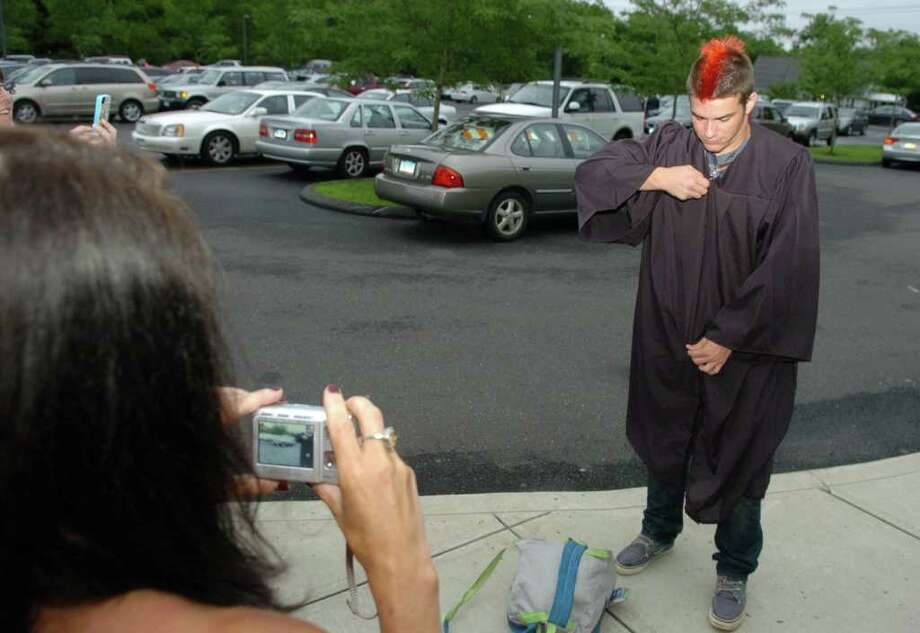 Highlights from Fairfield Warde High School's 7th Annual Commencement Exercises in Fairfield, Conn. on Wednesday June 23, 2011. Graduate Michael Sullivan puts his gown back on for family photos. Photo: Christian Abraham / Connecticut Post