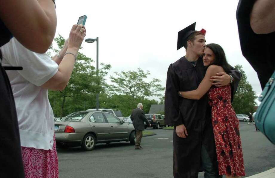 Highlights from Fairfield Warde High School's 7th Annual Commencement Exercises in Fairfield, Conn. on Wednesday June 23, 2011. Graduate Michael Sullivan kisses his mom Tonia as family takes photos. Photo: Christian Abraham / Connecticut Post