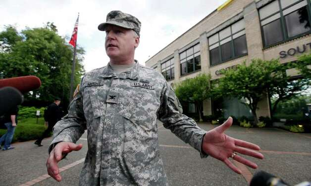 Col. Anthony Wright speaks with media members outside a federal building that houses the Seattle Military Processing Center Thursday, June 23, 2011, in Seattle. Two men have been arrested in a plot to use machine guns and grenades in an attack on the military recruiting station there that also houses a daycare, the U.S. Justice Department said Thursday. Abu Khalid Abdul-Latif, also known as Joseph Anthony Davis, of Seattle, and Walli Mujahidh, also known as Frederick Domingue Jr., of Los Angeles, were arrested Wednesday night. Photo: AP