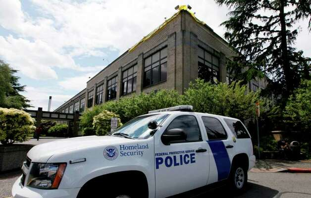 A police vehicle is parked outside a federal building that houses the Seattle Military Processing Center Thursday, June 23, 2011, in Seattle. Two men have been arrested in a plot to use machine guns and grenades in an attack on the military recruiting station there that also houses a daycare, the U.S. Justice Department said Thursday. Abu Khalid Abdul-Latif, also known as Joseph Anthony Davis, of Seattle, and Walli Mujahidh, also known as Frederick Domingue Jr., of Los Angeles, were arrested Wednesday night. Photo: AP