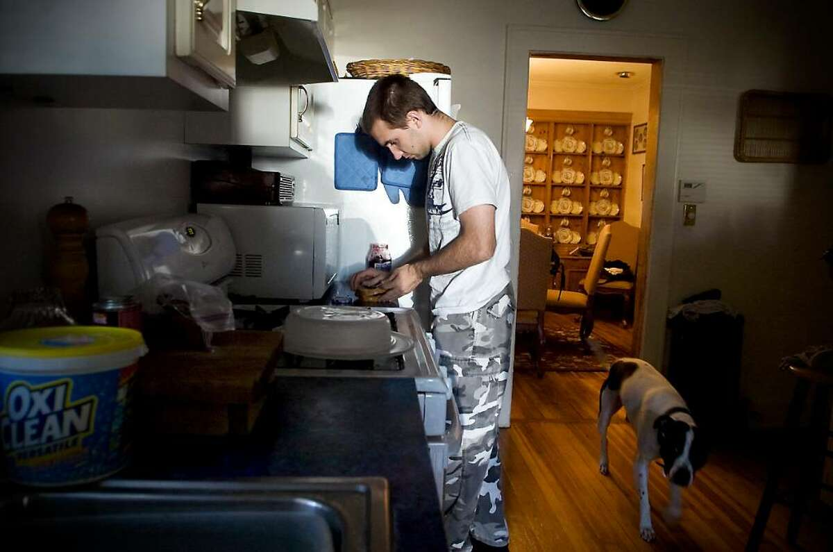 Myles Scott who has difficulty with language processing, finished his senior year at Westhill High School, but because he only reads at a third-grade level, his mother, Lori, fought to have him placed, at district expense, in a special school in Milford. Myles makes a snack after returning from his MIlford school at home in Stamford, Conn. on Thursday, Sept. 24, 2009.