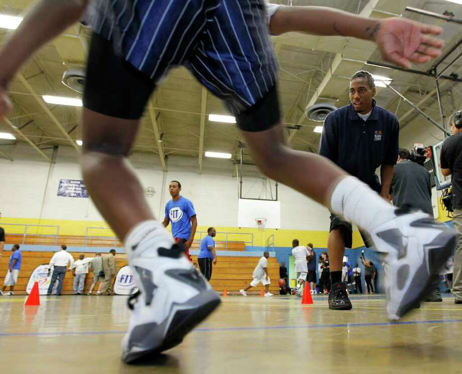 Kawhi Leonard, right, an NBA Draft prospect from San Diego State, looks on as Desean Johnston, 13, runs drills during a basketball clinic at the Boys & Girls Club, Wednesday, June 22, 2011 in Newark, N.J. Photo: AP