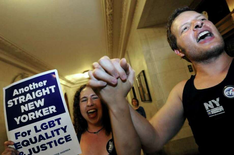 Protestors in favor of a same sex marriage bill  Julia Burke.left, and Jonathan Childress both of Buffalo demonstrate outside the State Senate at the Capitol in Albany, NY Thursday June 23, 2011( Michael P. Farrell/Times Union ) Photo: Michael P. Farrell