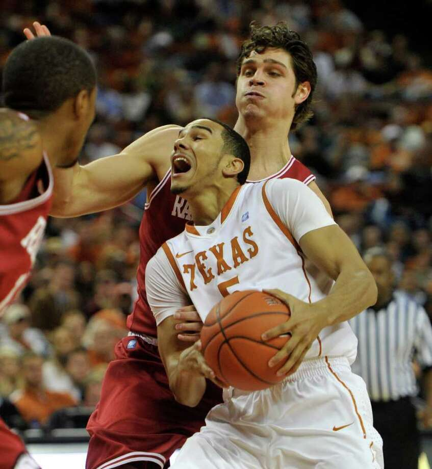 Texas guard Cory Joseph, front, drives past Arkansas forward Michael Sanchez, back, and guard Marcus Britt, left, during the first half in an NCAA college basketball game Tuesday, Jan. 4, 2011, in Austin, Texas. (AP Photo/Michael Thomas) Photo: Associated Press