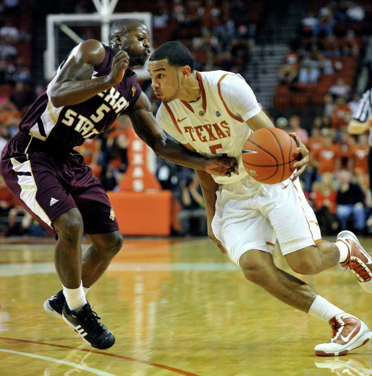 Texas guard Cory Joseph, right, drives past Texas State forward John Bowman, left, during the first half in an NCAA college basketball game, Saturday, Dec. 11, 2010, in Austin, Texas. (AP Photo/Michael Thomas)