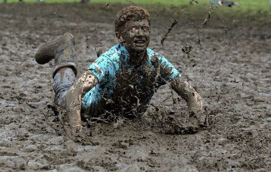 Tom Wilder, 17 from Kent, dives in the mud at the Glastonbury Festival site at Worthy Farm, Pilton in Glastonbury, England,  on Thursday, June 23, 2011. Music fans had to brave more rain at the five-day festival which opened Wedmesday. This year the festival will feature headline acts U2, Coldplay and Beyonce. The festival, which started in 1970 when several hundred hippies paid 1 British pound to watch Marc Bolan, has grown into Europe's largest music festival, attracting more than 175,000 people over five days. Photo: Matt Cardy, Getty Images / 2011 Getty Images