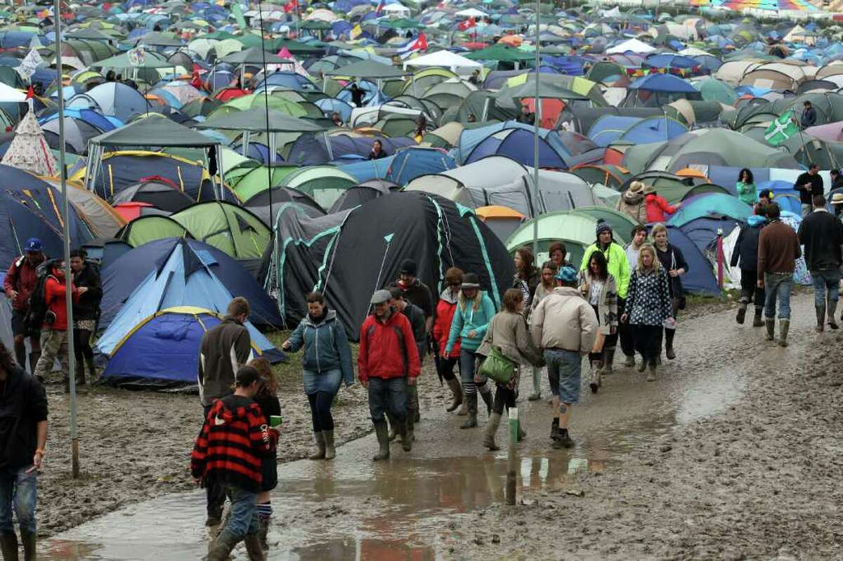 Festival goers move around the fields of tents.
