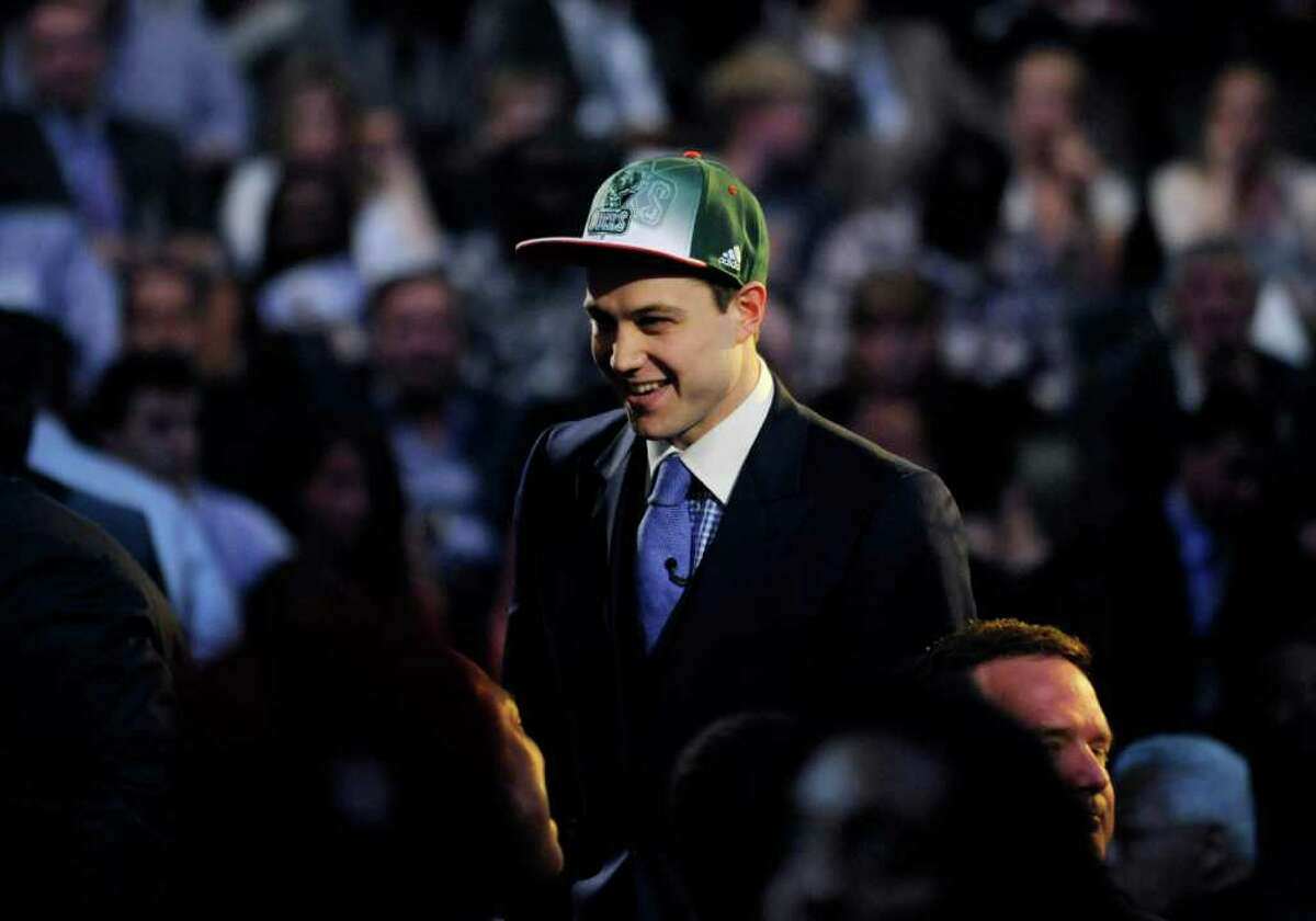 CORRECTS NAME OF PHOTOGRAPHER - The No. 10 overall draft pick, BYU's Jimmer Fredette, who was selected by the Milwaukee Bucks, smiles during the NBA basketball draft Thursday, June, 23, 2011, in Newark, N.J.