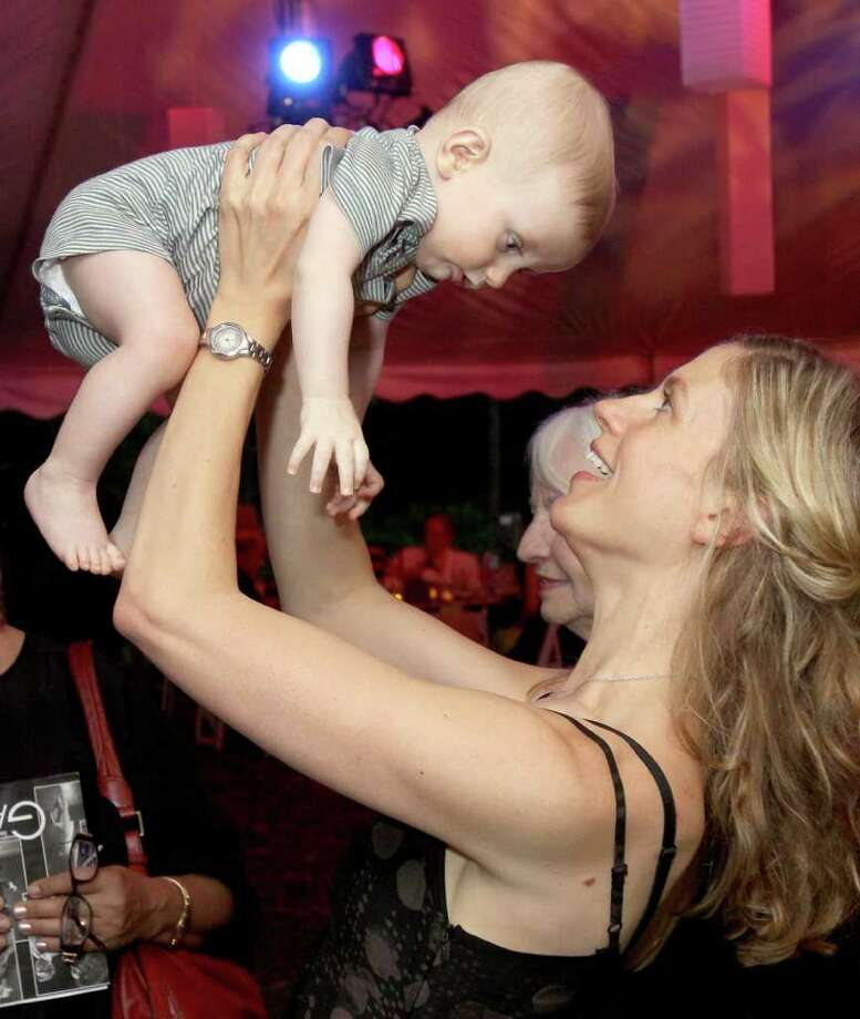 Beckett, MA - June 18, 2011 - (Photo by Joe Putrock/Special to the Times Union) - After being presented with the fifth annual Jacob's Pillow Dance Award, Kidd Pivot Frankfurt RM Choreographer and Artistic Director Crystal Pite (right) playes with her six month old son, Niko Taylor(left), during the Jacob's Pillow 2011 Season Opening Gala. Photo: Joe Putrock / Joe Putrock