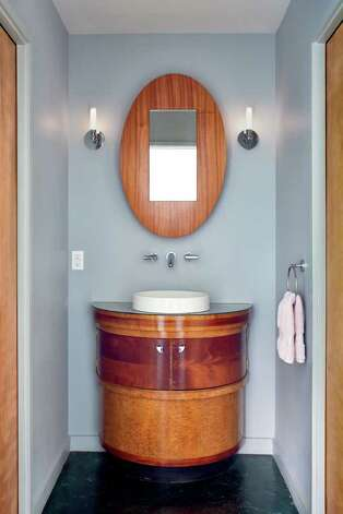 The bathroom vanity was fashioned from a vintage art deco stand originally made for a beauty salon.  The custom mirrored cabinet above was fabricated by local furniture artist Peter Zubiate. Photo: CHRIS COOPER/Special To The Express-News / © 2010 Chris Cooper all rights reserved