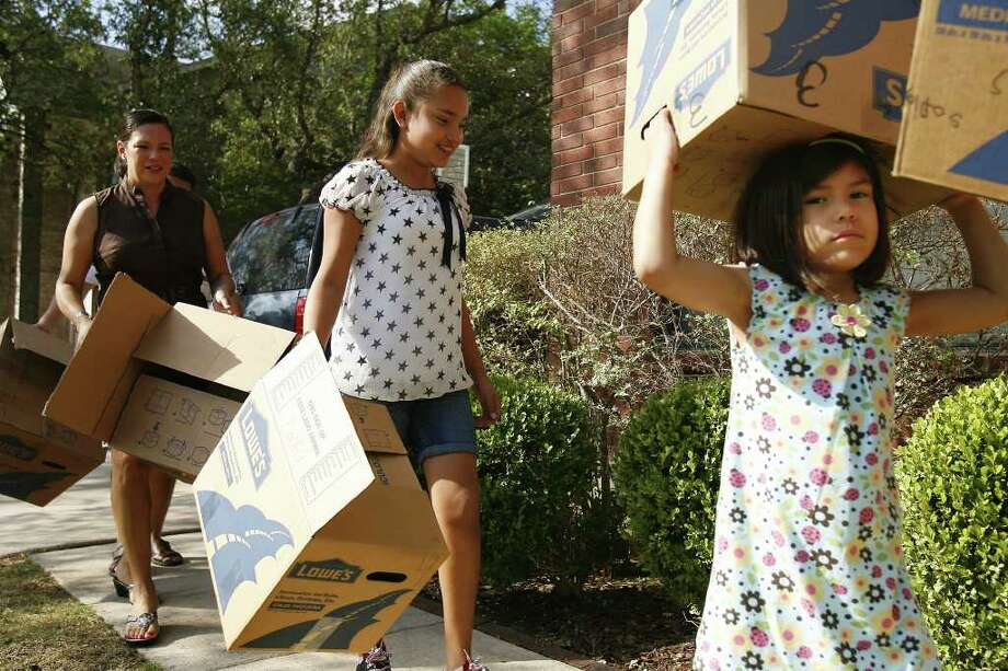 Yolanda Flores (from left) and daughters Lilliana Flores, 11, and Sofia Flores, 4, carry empty boxes into their house one Emerald Hill Drive. Yolanda says it's hard moving and selling with kids because they have to stay entertained. Photo: SALLY FINNERAN, SAN ANTONIO EXPRESS-NEWS / sfinneran@express-news.net