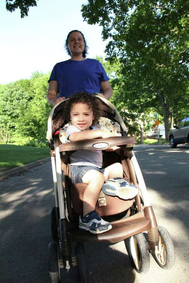 Angel Montanez, age 22 months of Troy, in stroller, and Kelly Hull, of Troy, get active on a walk in their Troy neighborhood on Monday, June 20, 2011. (Erin Colligan / Special To The Times Union) / 00013568A