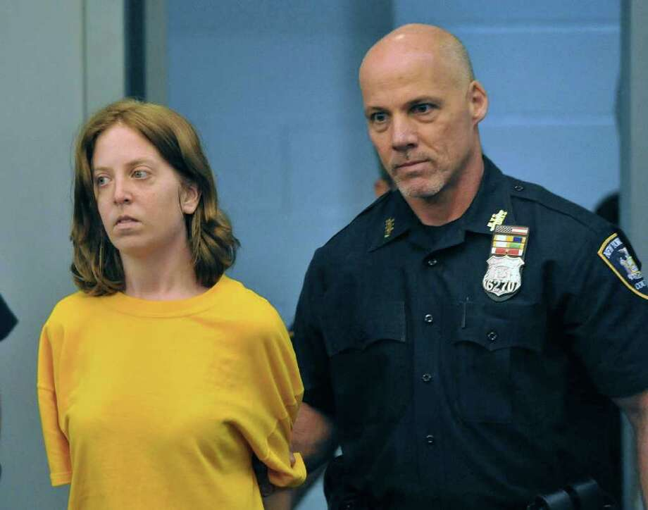 Melinda Brady, wife of David Laffer, who is accused of killing four people in a pharmacy robbery is led into Suffolk County District Court on Friday, June 24, 2011, in Central Islip, New York. Brady was arraigned on charges of robbery and obstructing governmental administration in connection with the Father's Day shootings at Haven Drugs in Medford, on Long Island.(AP Photo/Kathy Kmonicek) Photo: Kathy Kmonicek