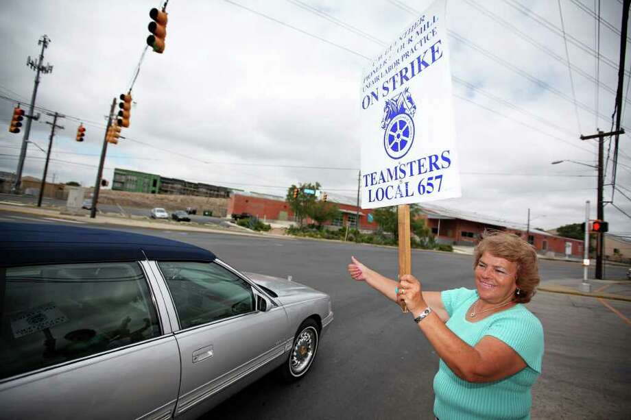 C.H. Guenther & Son Inc. employee Maria Martinez gives a thumbs up to a passing car while picketing outside of the flour mill on South Alamo Street. June 25 marked the two-month anniversary of the strike. Photo: ANDREW BUCKLEY, SAN ANTONIO EXPRESS-NEWS / abuckley@express-news.net