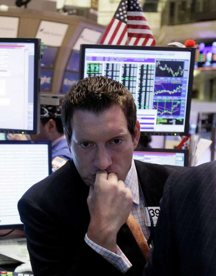 In this June 22, 2011 photo, specialist William Bott looks at a screen as he works on the floor of the New York Stock Exchange. World stock markets climbed Friday, June 24, after the European Union offered billions of euros in funds to help recession-mired Greece avoid a massive debt default. (AP Photo/Richard Drew) Photo: Richard Drew