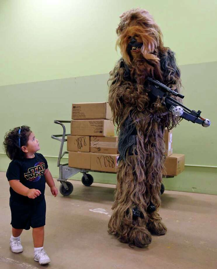 Sabrina Leia, 2, (left)  looks at Anthony Edwards, 17, dressed as Chewbacca. Photo: Edward A. Ornelas/Express-News / © SAN ANTONIO EXPRESS-NEWS (NFS)