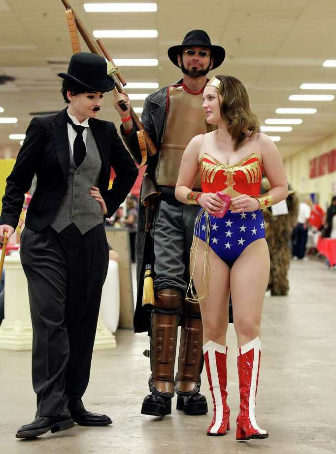April Morgan, 27, as Charlie Chaplin (from left) N. Rivera, 45, as a Steampunk Rifleman,  and Lauren Morgan, 23,  as Wonder Woman take in the sights. Photo: Edward A. Ornelas/Express-News / © SAN ANTONIO EXPRESS-NEWS (NFS)