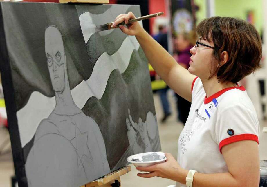 Artist Amanda Rogers, 28, works on a painting of Captain America, which is up for bid in a silent auction benefitting the Fisher House, during the Texas Comicon 2011 Friday June 24, 2011 at the San Antonio Event Center. The comicon runs through Sunday. Photo: Edward A. Ornelas/Express-News / © SAN ANTONIO EXPRESS-NEWS (NFS)