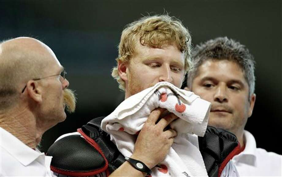 Houston Astros catcher J.R. Towles, center, is helped off the field after being cut on the face by a foul ball during the third inning of an interleague baseball game against the Tampa Bay Rays, Friday, June 24, 2011, in Houston. (AP Photo/David J. Phillip) Photo: Associated Press