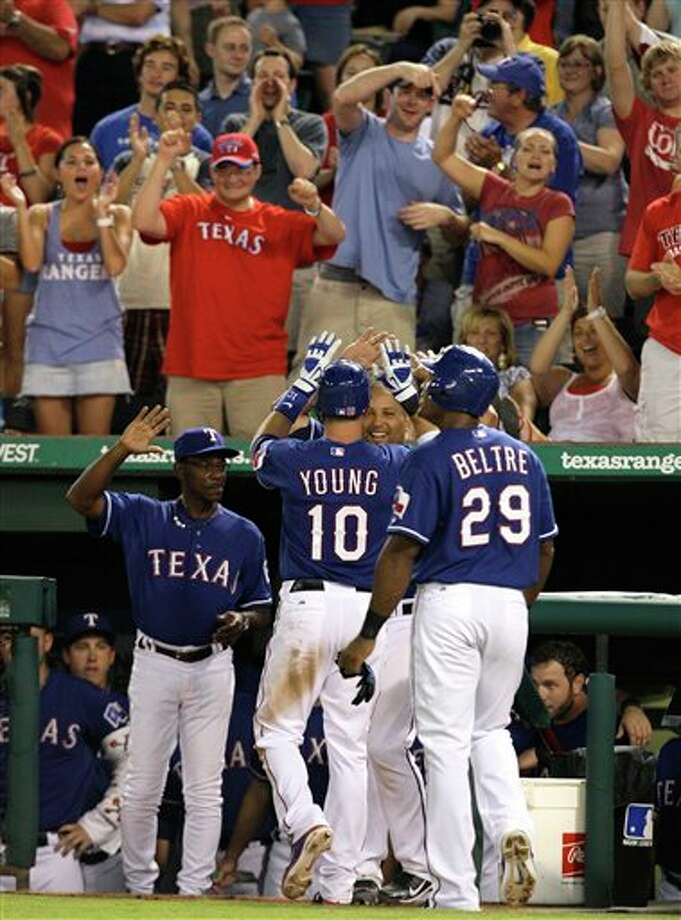 Fans cheer as Texas Rangers' Michael Young (10) is congratulated at the dugout by Yorvit Torrealba, right rear, and manager Ron Washington, left, after hitting a two-run home run that scored Adrian Beltre (29) in the seventh inning of an interleague baseball game against the New York Mets, Friday, June 24, 2011, in Arlington, Texas. (AP Photo/Tony Gutierrez) Photo: Associated Press