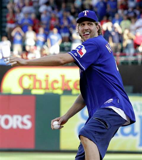 Dallas Mavericks' Dirk Nowitzki, of Germany, throws out the honorary first pitch before the start of
