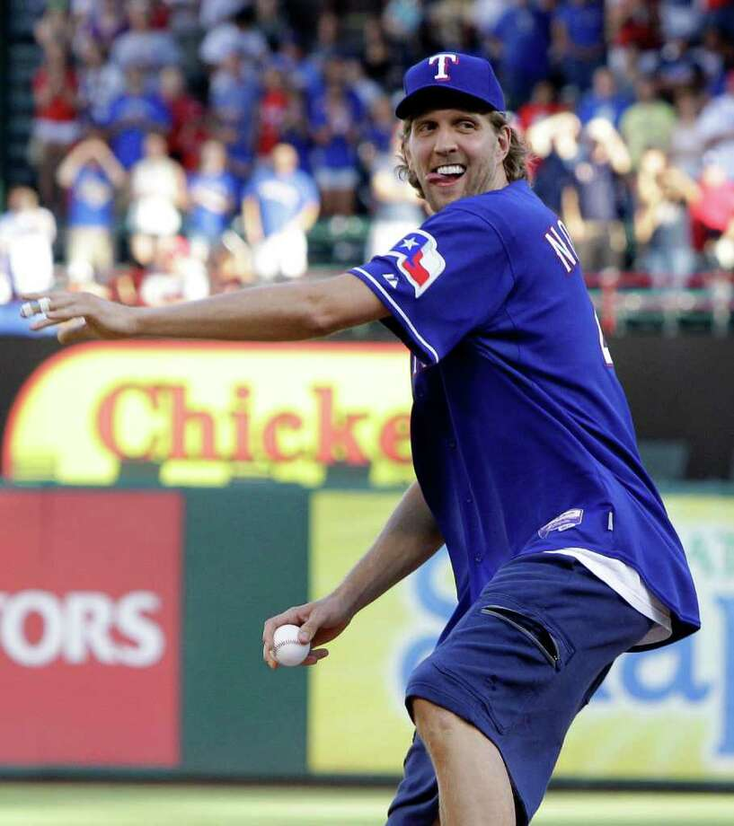 Dallas Mavericks' Dirk Nowitzki, of Germany, throws out the honorary first pitch before the start of an interleague baseball game between the New York Mets and the Texas Rangers, Friday, June 24, 2011, in Arlington, Texas. (AP Photo/Tony Gutierrez) Photo: Tony Gutierrez