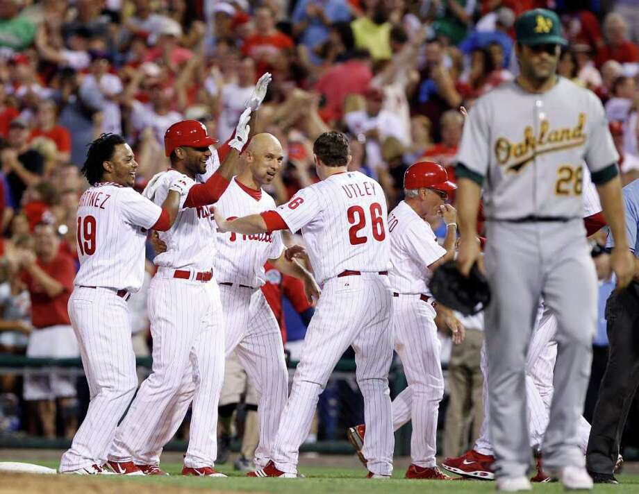 From left to right, Philadelphia Phillies' Michael Martinez, Ben Francisco, Raul Ibanez and Chase Utley celebrate after Francisco's game-winning RBI-single in the ninth inning of a baseball game against the Oakland Athletics, Friday, June 24, 2011, in Philadelphia. Athletics first baseman Conor Jackson, right, looks on. Philadelphia won 1-0. (AP Photo/Matt Slocum) Photo: Matt Slocum