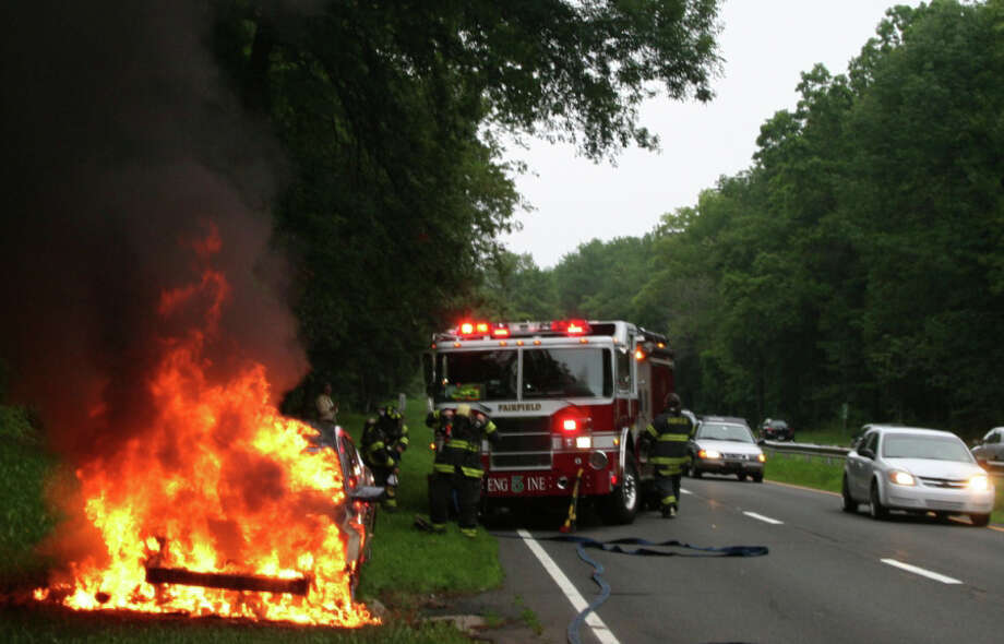 A car burst into flames on the Merritt Parkway at the Fairfield-Westport border Friday night, but the driver was able to get out of the southbound Nissan Altima without being injured. Photo: Contributed Photo/Fairfield Fire Department / Fairfield Citizen contributed