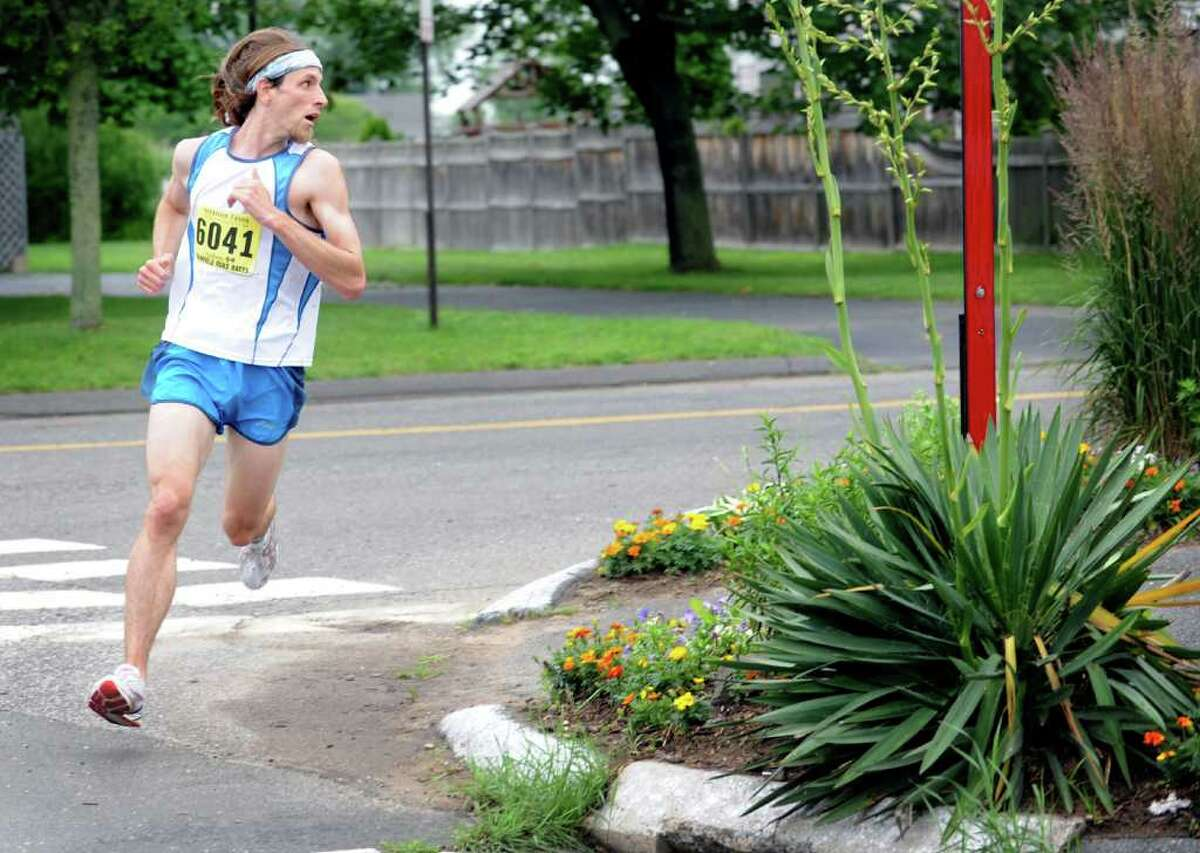 Timothy Milenkevich, of Ansonia, looks back at the competition as he runs the Stratton Faxon Fairfield 5K Saturday, June 25, 2011. Milenkevich finished the race in first place with a time of 16:07.