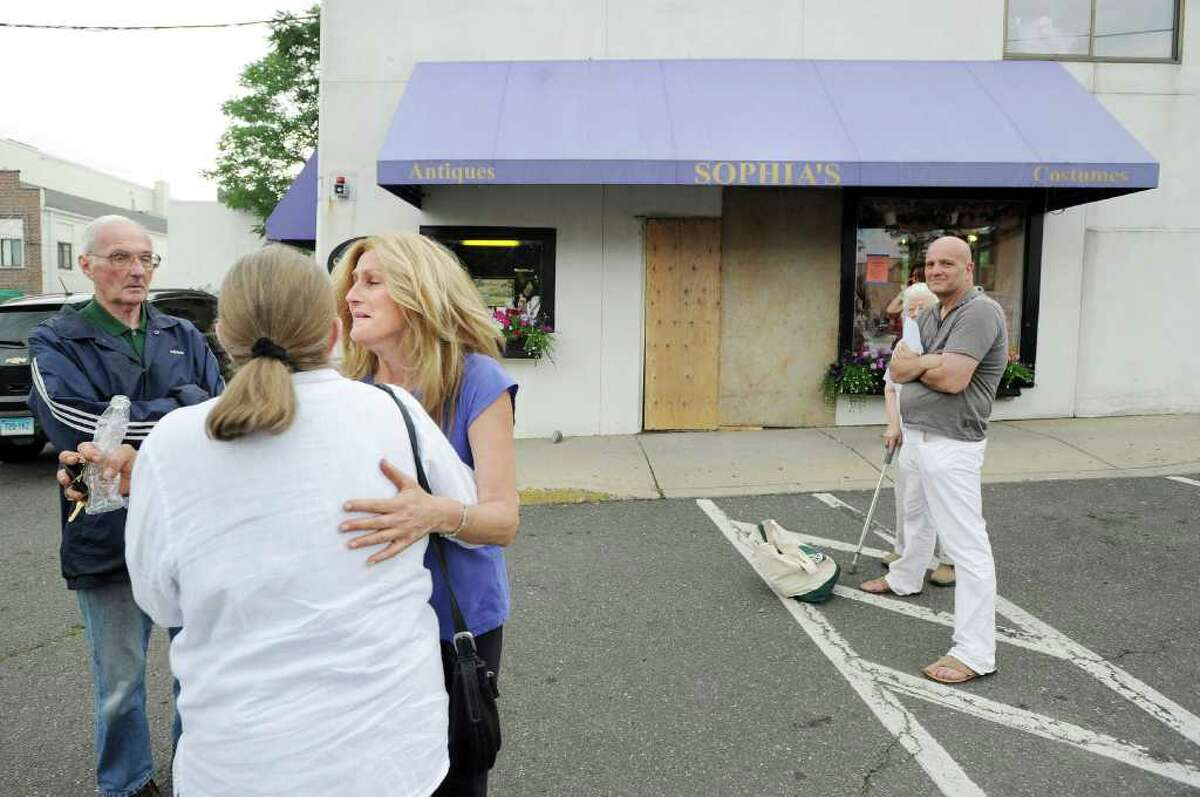 Sophia Scarpelli, third from left, owner of Sophia's Costumes (background) at 1 Liberty Way in downtown Greenwich, reacts while being comforted by friends after a car drove through the front of her store late Saturday morning, June 25, 2011.