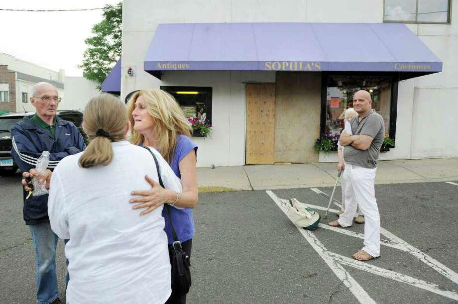 Sophia Scarpelli, third from left, owner of Sophia's Costumes (background) at 1 Liberty Way in downtown Greenwich, reacts while being comforted by friends after a car drove through the front of her store late Saturday morning, June 25, 2011. Photo: Bob Luckey / Greenwich Time