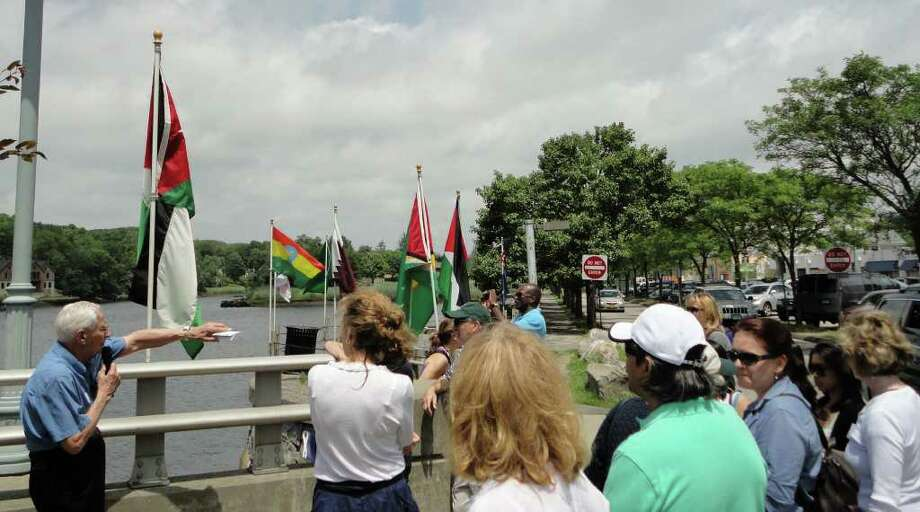 Visitors to Westport from the United Nations on Saturday get a tour of the downtown area from town historian Allen Raymond as flags of many of the nations flap in the breeze along the banks of the Saugatuck River. Photo: Meg Barone / Westport News freelance