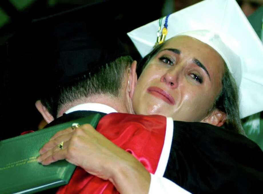 Rachel Gioia lets her emotions go as she hugs New Milford HIgh School teacher Stephen Flanagan moments after receiving her diploma at the school's commencement exerices on the westside campus of Western Connecticut State Unviersity in Danbury. Photo: Norm Cummings / The News-Times