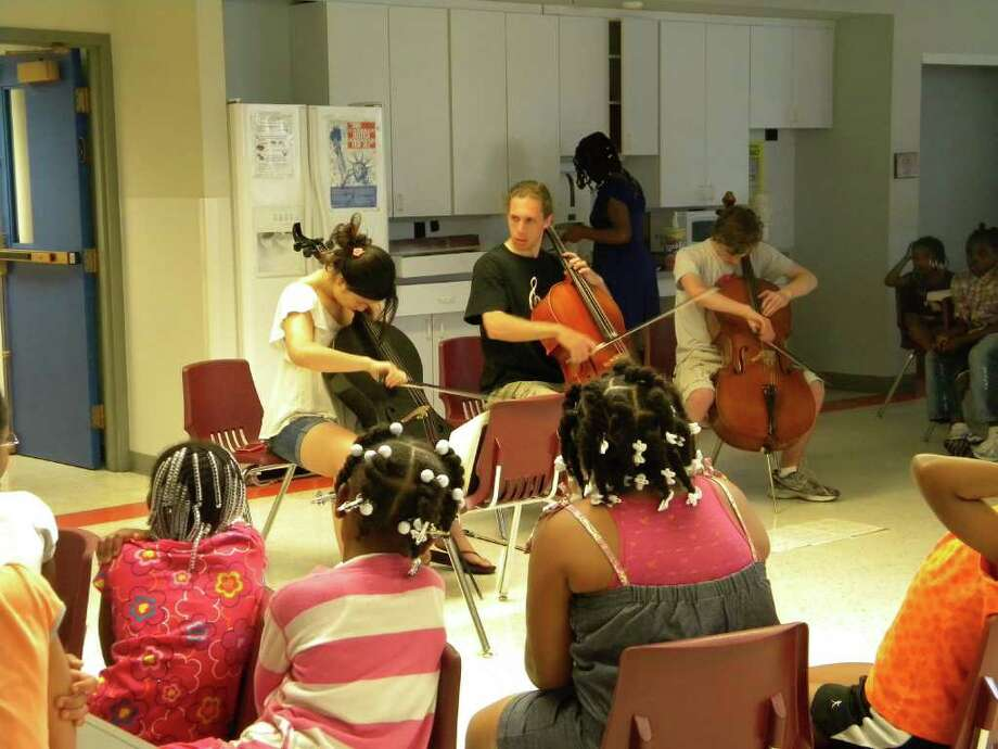 Members of an ESYO cello trio perform for their audience at Girls, Inc.