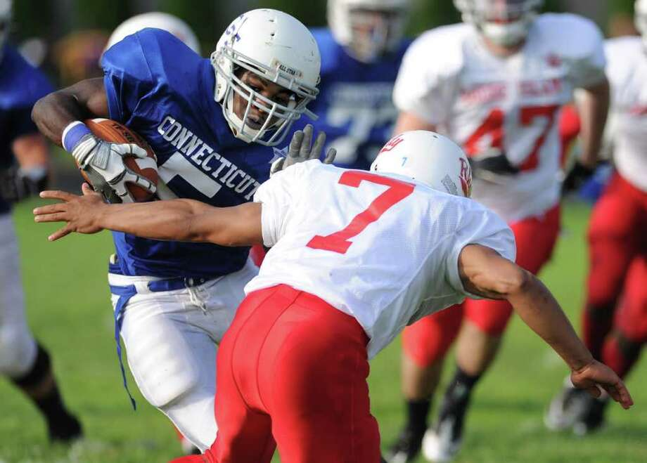 Ansonia High School's Montrell Dobbs carries the ball as he avoids Rob Delgado and runs for a touchdown during the Connecticut High School football all-star game against Rhode Island on June 25, 2011, at Southington High School. Photo: Lindsay Niegelberg / Connecticut Post