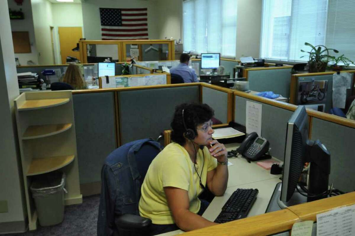 Utility Consumer Assistance Specialist Susie Baker works with fellow employees fielding phone calls at the New York State Public Service Commission call center on Thursday June 23, 2011 in Delmar, NY. ( Philip Kamrass / Times Union)