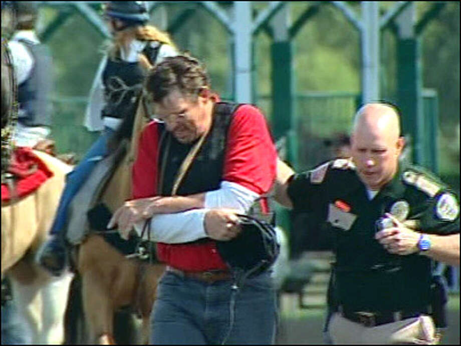 A security guard escorts a handler away from the starting gates at Emerald Downs on Saturday after a horse went berserk and slammed him against the gate. An earlier incident at the track injured three people.