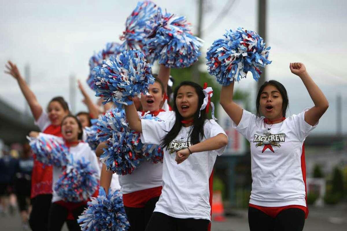 Cheerleaders from Chief Sealth High School help push runners during the Dodge Rock 'n' Roll Seattle Marathon & Half Marathon.