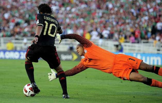 Mexico's Giovani Dos Santos, left, moves the ball around U.S. goalkeeper Tim Howard just before scoring during the second half of the CONCACAF Gold Cup soccer final against the United States, Saturday, June 25, 2011, in Pasadena, Calif. Mexico won 4-2. (AP Photo/Mark J. Terrill) Photo: Associated Press