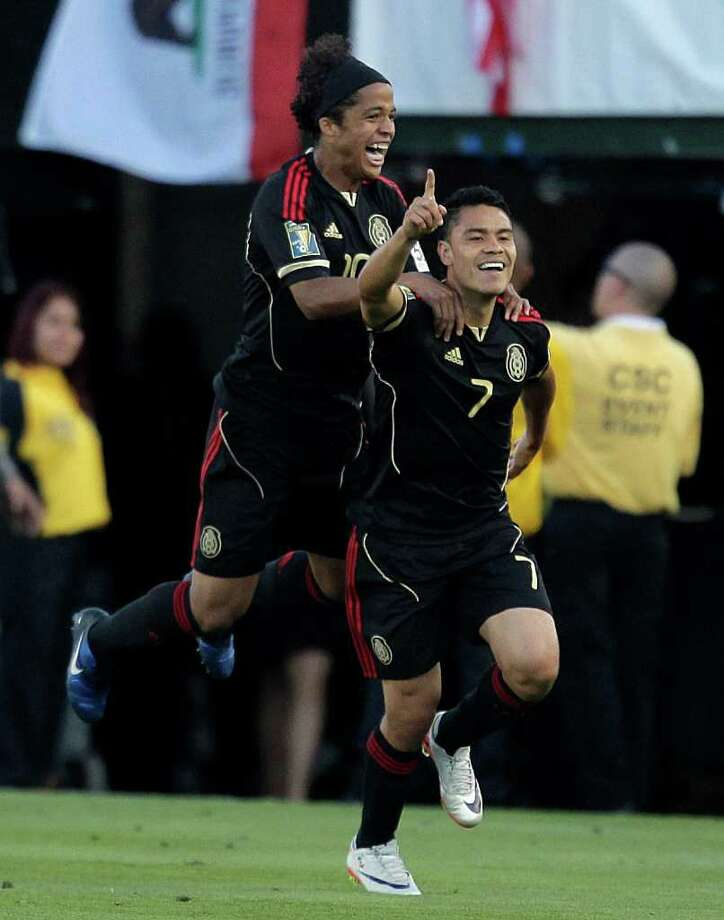Mexico's Pablo Barrera (7) and Giovani Dos Santos celebrate after Barrera scored against United States during the second half of the CONCACAF Gold Cup soccer final at the Rose Bowl in Pasadena, Calif., Saturday, June 25, 2011. (AP Photo/Jae C. Hong) Photo: Associated Press