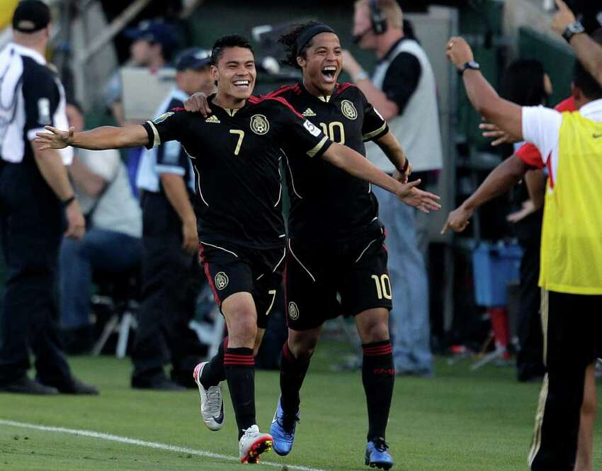 Mexico's Pablo Barrera, left, and Giovani Dos Santos celebrate after Barrera scored against United States during the second half of the CONCACAF Gold Cup soccer final game at the Rose Bowl in Pasadena, Calif., Saturday, June 25, 2011. (AP Photo/Jae C. Hong)