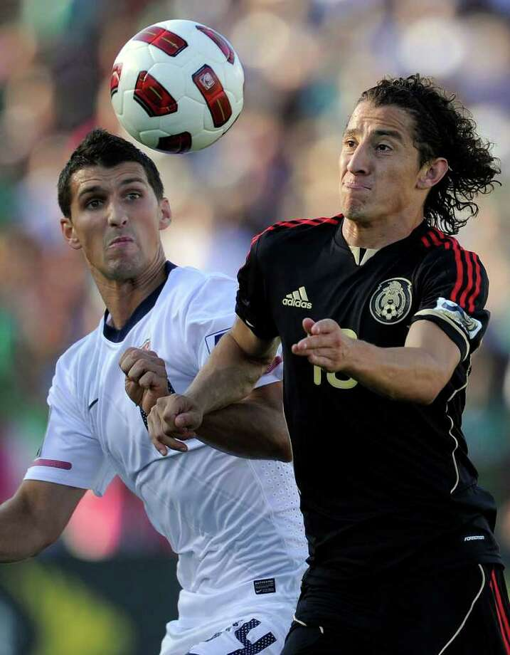 United States' Eric Lichaj, left, and Mexico's Andres Guardado eye the ball during the first half of the CONCACAF Gold Cup soccer final, Saturday, June 25, 2011, in Pasadena, Calif. (AP Photo/Mark J. Terrill) Photo: Associated Press