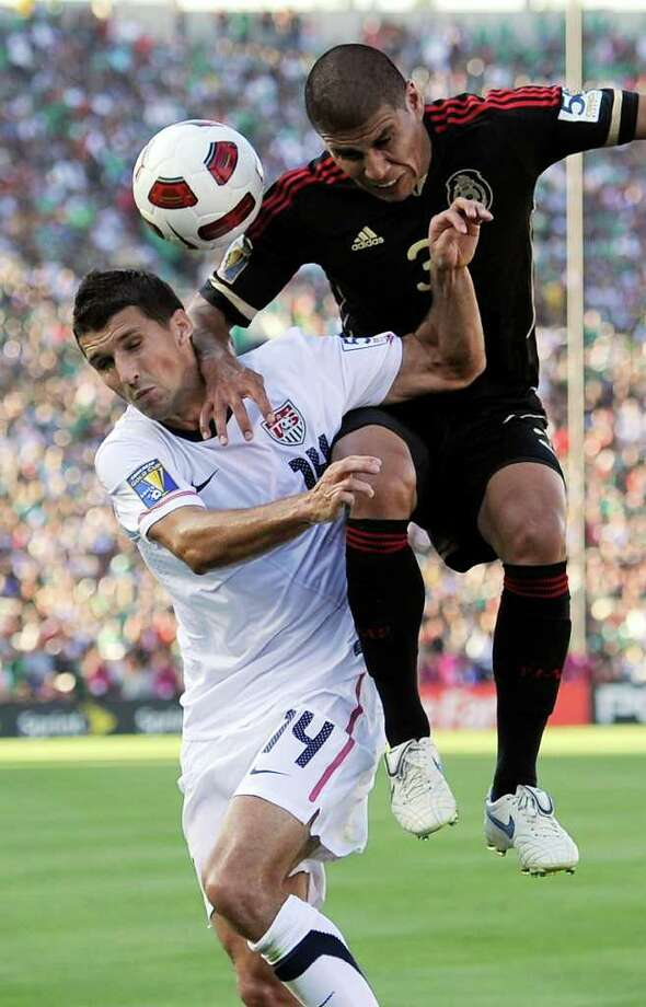 United States' Eric Lichaj, left, and Mexico's Carlos Salcido vie for the ball during the first half of the CONCACAF Gold Cup soccer final, Saturday, June 25, 2011, in Pasadena, Calif. (AP Photo/Mark J. Terrill) Photo: Associated Press