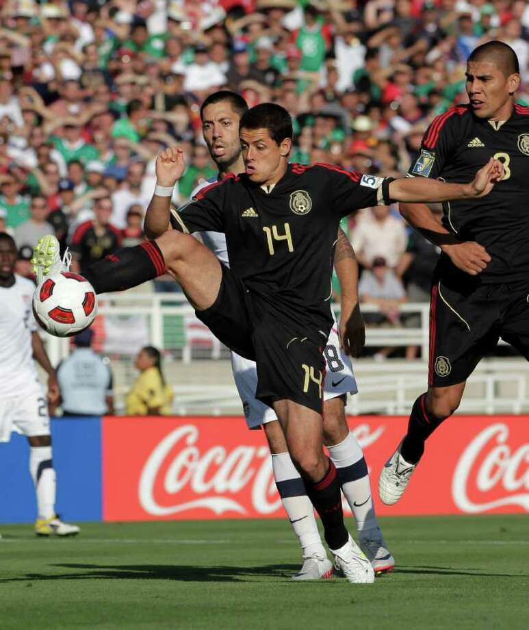 United States' Clint Dempsey, rear, defends Mexico's Javier Hernandez (14) during the first half of the CONCACAF Gold Cup soccer final at the Rose Bowl in Pasadena, Calif., Saturday, June 25, 2011. (AP Photo/Jae C. Hong) Photo: Associated Press
