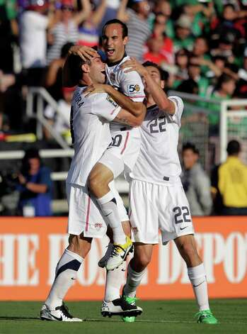United States' Landon Donovan, center, is congratulated by Carlos Bocanegra, left, and Alejandro Bedoya after Donovan scored against Mexico during the first half of the CONCACAF Gold Cup soccer final at the Rose Bowl in Pasadena, Calif., Saturday, June 25, 2011. (AP Photo/Jae C. Hong) Photo: Associated Press
