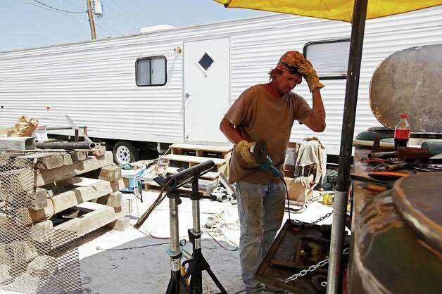 Welder Landy Trapp works on his welding truck while living at an RV Park on the outskirts of Carrizo Springs, Texas, Thursday, June 9, 2011. Trapp stayed in his vehicle for the first two nights after arriving in the city three months ago. There were no hotel rooms available. He rents the RV for $325 a week and it serves as home for his family.  Demand for living space shot up throughout small towns on the Eagle Ford play. Oilfield related companies are finding it hard to find accommodations for their workers. Trapp moved to the area from Kenedy, Texas and hopes to land a job that will last 6-8 months. JERRY LARA/glara@express-news.net Photo: JERRY LARA, Jerry Lara/Express-News / SAN ANTONIO EXPRESS-NEWS
