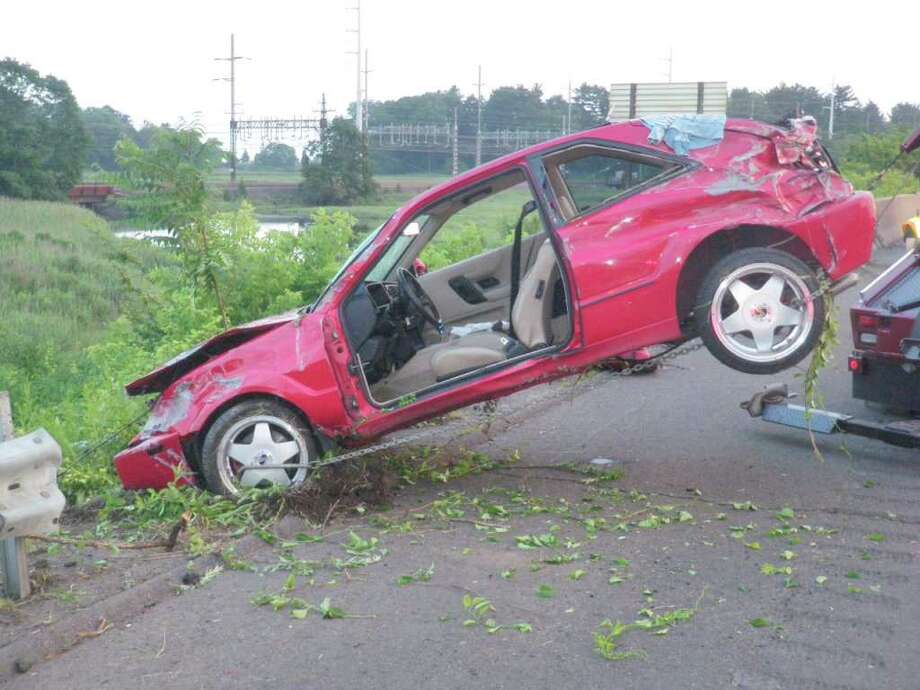 The driver-side door was torn off this Volkswagen Corrado Saturday night when it crashed through an Interstate 95 guardrail, careened down an embankment and stopped near Sasco Creek. Photo: Contributed Photo/Westport Fire Department / Westport News contributed