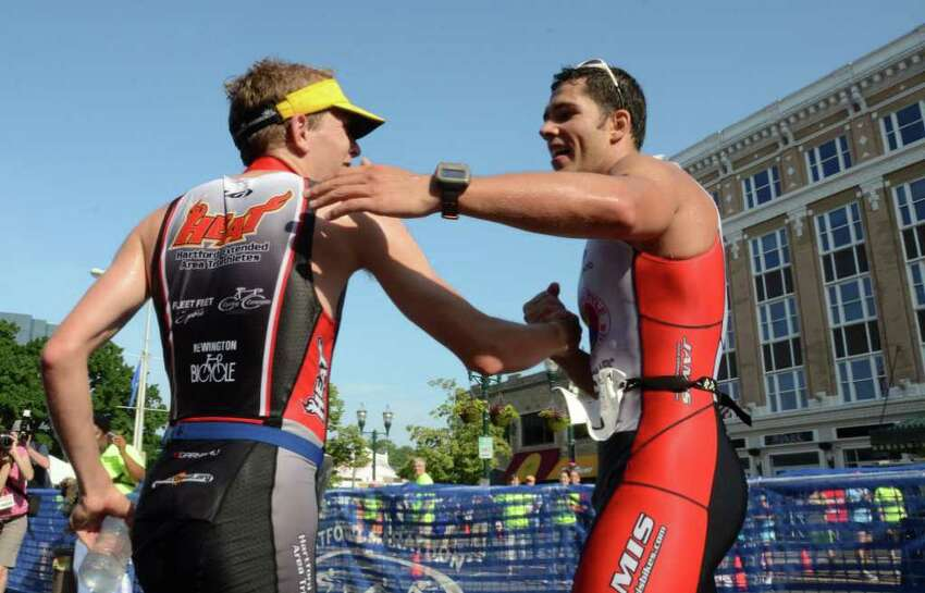 Last years winner, Andrew Kalley, of New York, at right, reaches out to congratulate first place finisher Thomas McWalters, of Hartford, during the Stamford KIC IT Triathlon in Columbus Park Sunday June 27, 2010. The race features a mile swim off of Cummings Beach followed by a 24.8 mile bike throughout the city and a 6 mile run finishing at Columbus Park. The event drew more than 500 athletes raising money for Greenwich based Kids in Crisis.