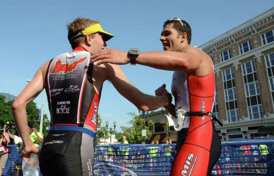 Last years winner, Andrew Kalley, of New York, at right, reaches out to congratulate first place finisher Thomas McWalters, of Hartford, during the Stamford KIC IT Triathlon in Columbus Park Sunday June 27, 2010. The race features a mile swim off of Cummings Beach followed by a 24.8 mile bike throughout the city and a 6 mile run finishing at Columbus Park. The event drew more than 500 athletes raising money for Greenwich based Kids in Crisis. Photo: Amy Mortensen / Connecticut Post Freelance