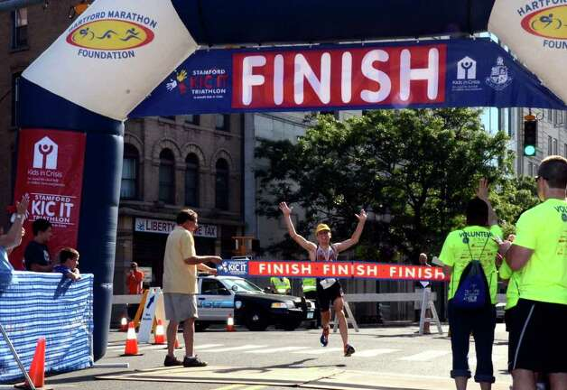 Thomas McWalters, of Hartford, crosses the finish line during the Stamford KIC IT Triathlon in Columbus Park Sunday June 27, 2010. The race features a mile swim off of Cummings Beach followed by a 24.8 mile bike throughout the city and a 6 mile run finishing at Columbus Park. The event drew more than 500 athletes raising money for Greenwich based Kids in Crisis. Photo: Amy Mortensen / Connecticut Post Freelance